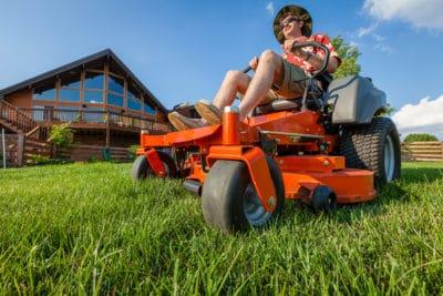 man on grass-cutting machine